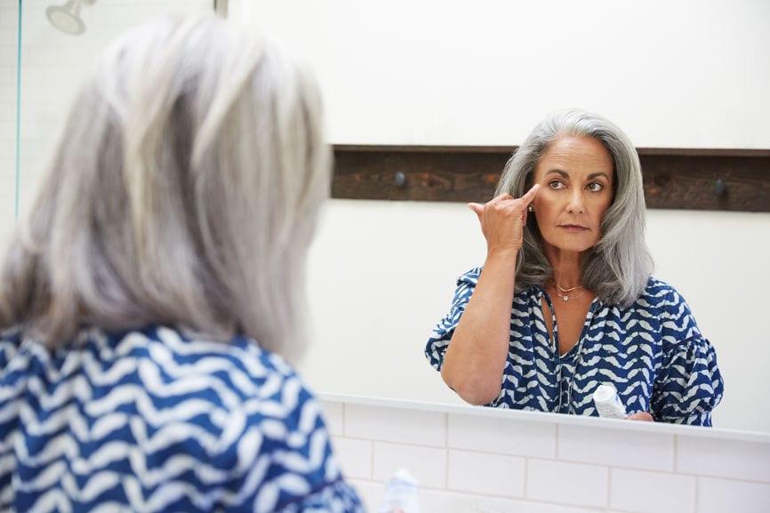 Senior Woman With Grey Hair Putting On Moisturizer In Bathroom Mirror