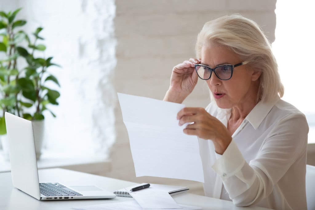 Confused senior businesswoman surprised reading paper letter
