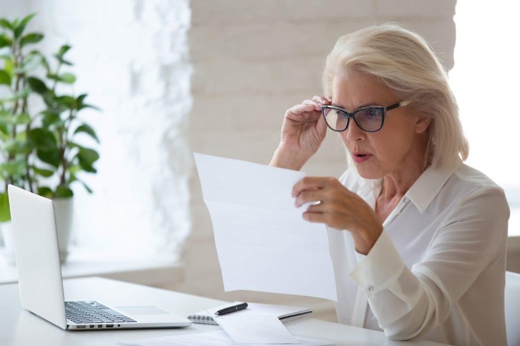 Confused senior businesswoman surprised reading paper letter